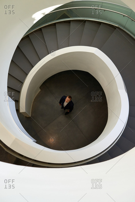 Directly above view of businessman standing under the spiral stairway and looking up