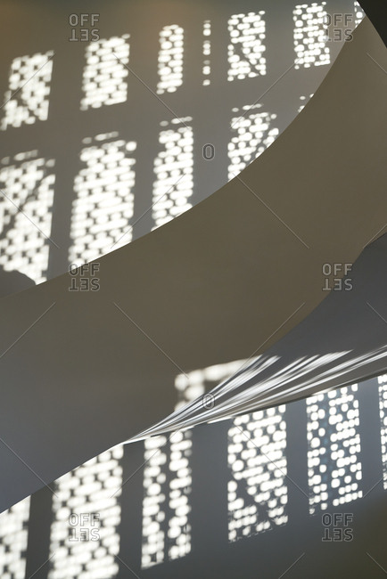 White circular staircase and wall with shadows from perforated panel in contemporary business center