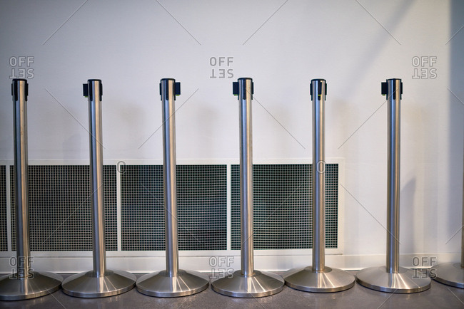 Row of steel retractable barriers without ropes standing on background of white wall with vent covers