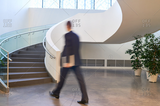 Rear view of businessman in suit walking towards spiral staircase in modern office building