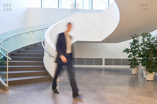 ... Businessman Moving Away From Winding Staircase In Contemporary Office  Building