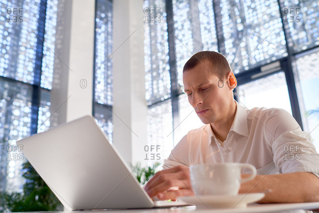 Low angle view of focused young man working on laptop while sitting in modern business center