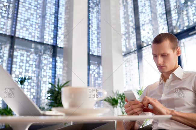 Serious young man reading news on smartphone while resting in modern business cafeteria with perforated fa�ade