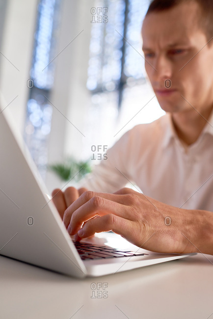 Close-up view of concentrated young man typing on laptop while sitting at table in cafe