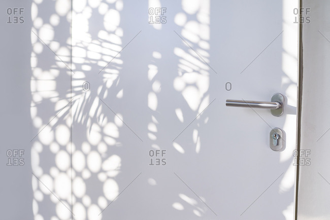 Close-up shot of white office door with shadow patterns from perforated window