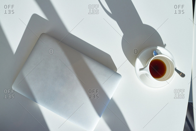 Directly above view of light silver laptop and half full cup of tea casting shadows on white table background