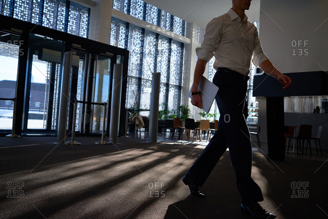 Low angle view of businessman with laptop walking down the hall of modern business center with perforated walls