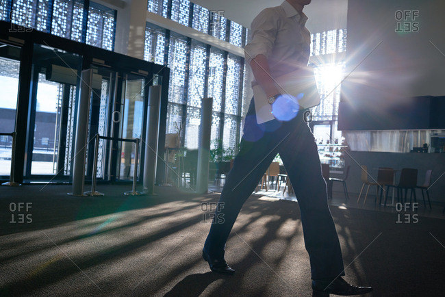 Low angle view of businessman with laptop going down the hall of contemporary office building while morning sun shining brightly