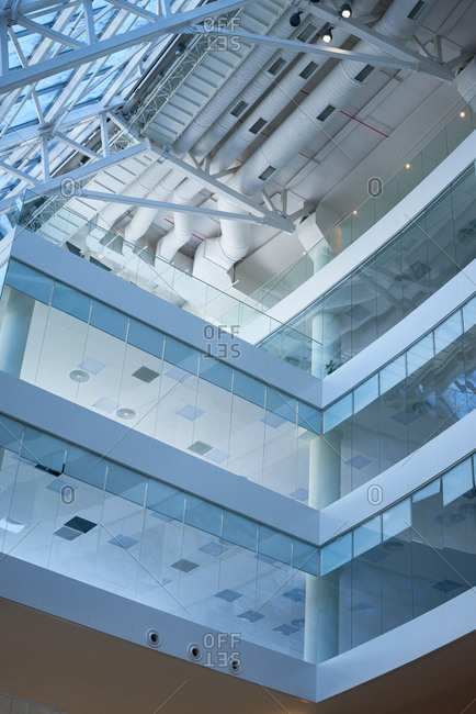 Interior of multi-storied contemporary business center with glass walls and roof