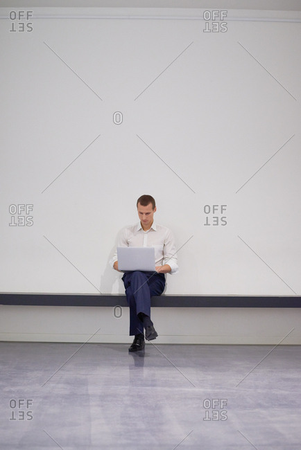Young man in formalwear working on laptop while sitting alone on modern bench with his legs crossed on white wall background