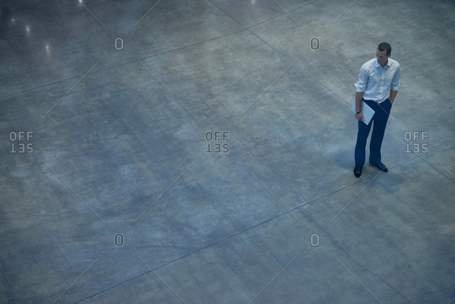 Young confident businessman standing alone in business hall