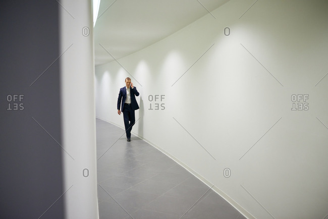 Young serious businessman in suit talking on the phone while walking down the curved corridor in new office building