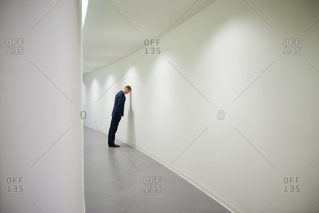 Young frustrated businessman in suit standing in office corridor with hands in pockets and leaning his head against wall
