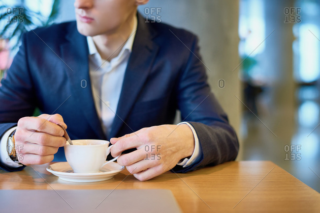 Close-up view of young pensive businessman in suit sitting in cafe with cup of coffee and looking to the side
