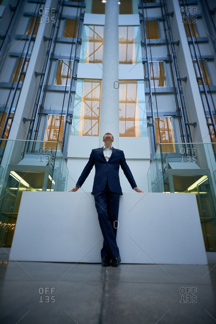 Low angle view of business man in suit standing on background of contemporary office building, leaning on massive pedestal and looking up proudly