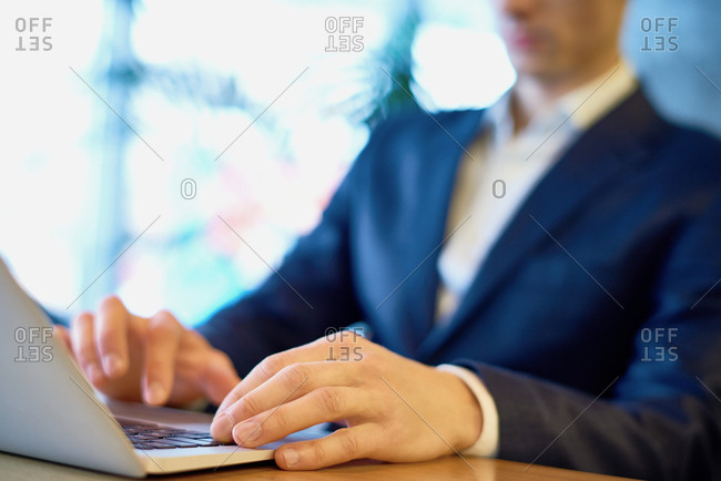 Close-up view of businessman in formal wear sitting at table and typing on laptop, focus on his hands