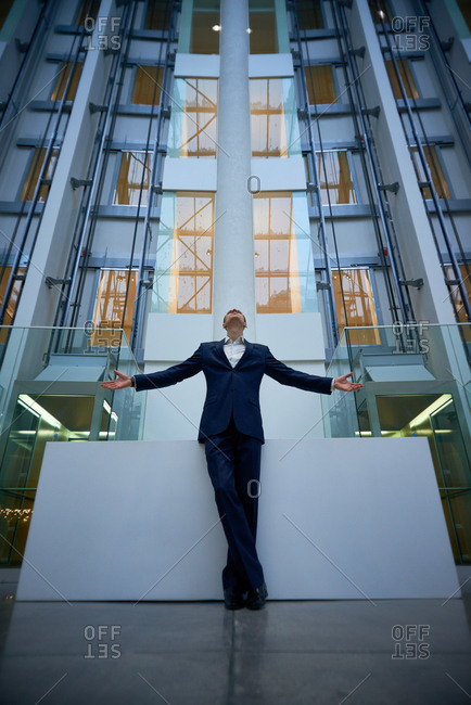 Low angle view of confident man in suit standing on background of modern luxurious business center with his arms outstretched and looking up proudly
