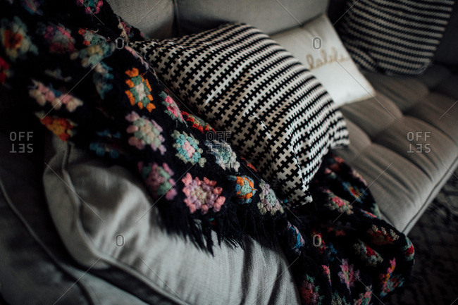 Crocheted blanket and pillow on couch