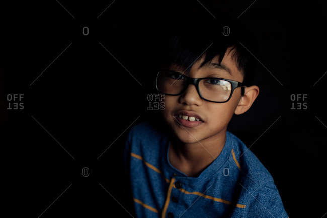 An Asian boy wearing glasses
