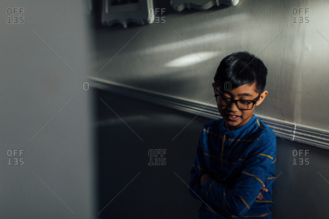 Boy with glasses standing in hallway