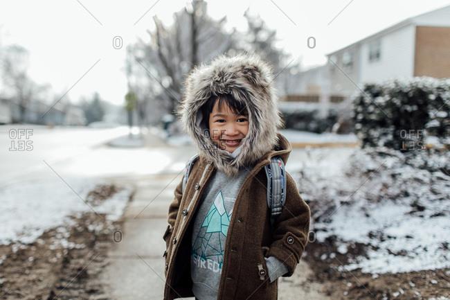 Boy in backpack and fur hood