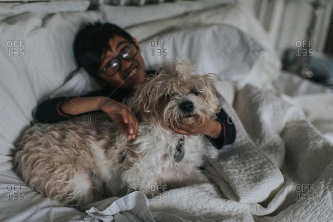 Boy and dog cuddling in bed