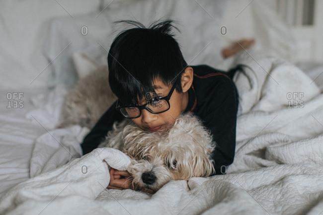Boy with glasses cuddling dog