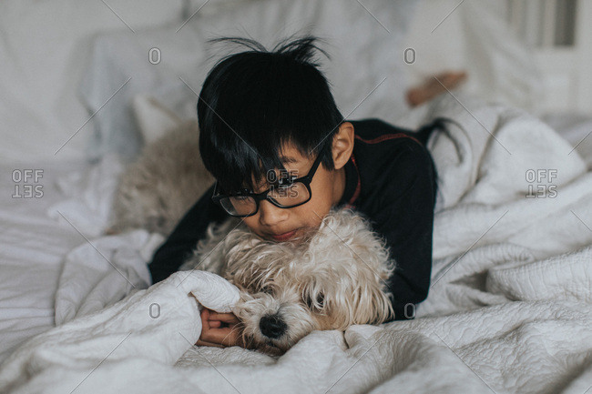 Boy with glasses cuddling dog