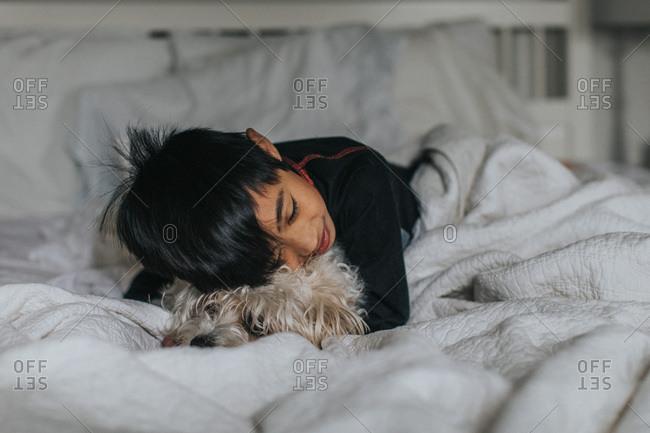 Boy cuddling on dog in bed