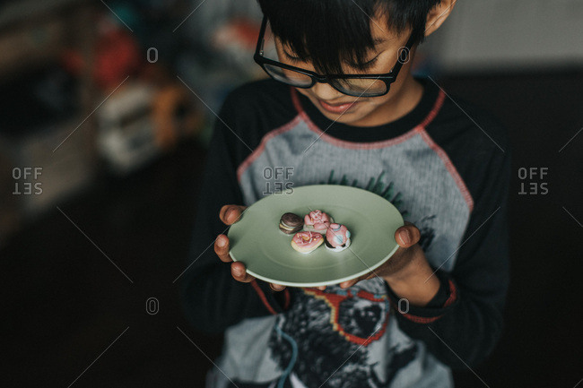 Boy looking at little desserts on plate