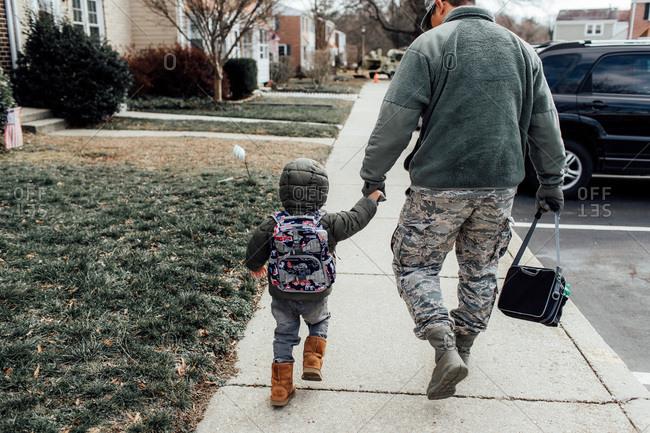 Military man walking with boy