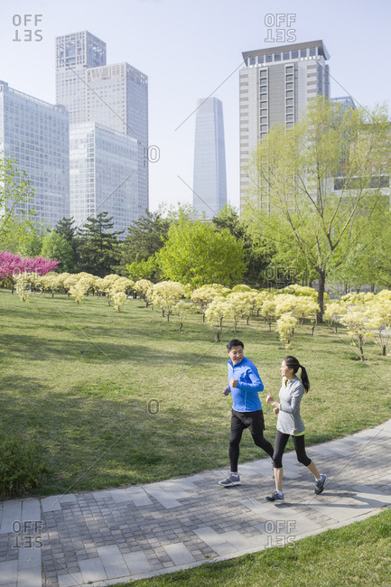 Happy mature couple running in park