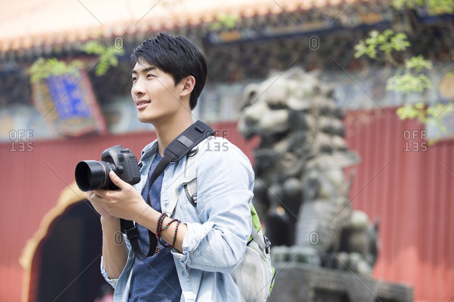 Young man travelling at the Lama Temple with camera