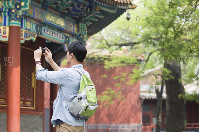 Young man taking pictures with smart phone in the Lama Temple