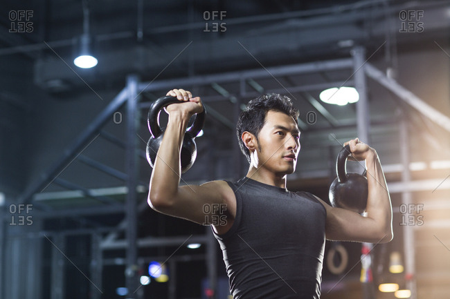 Young man training with kettle bells in  gym