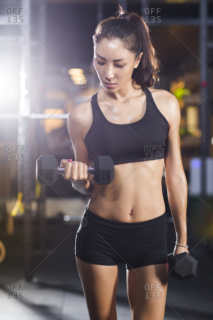 Young woman lifting weights at gym