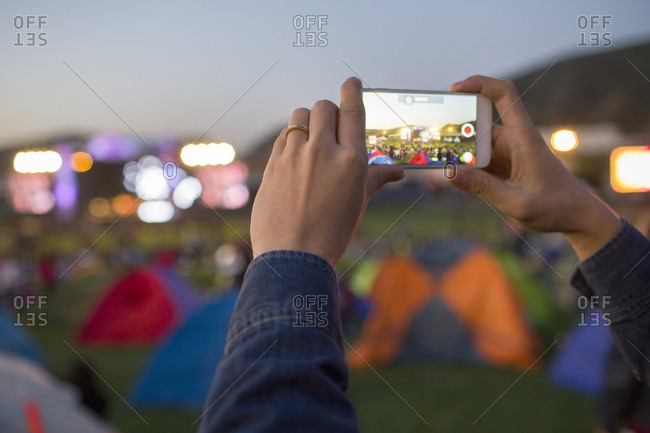 Young man taking photos with smart phone at music festival