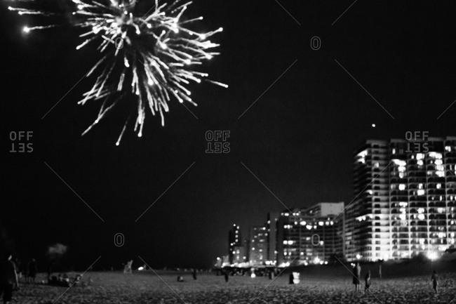 Fireworks bursting over a beach at night