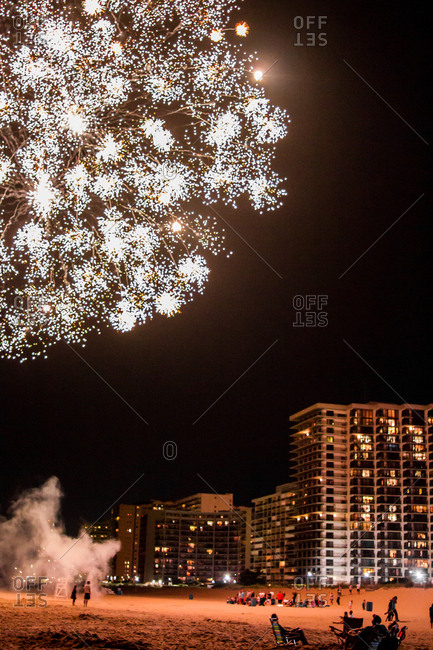 Fireworks bursting over resorts on a beach at night
