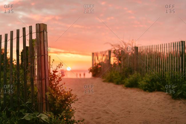 Fences and sand on a beach at sunrise