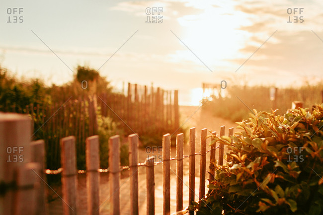 Beach access path between fences at sunrise