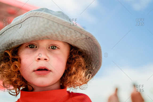 2bebba2c6 Boy with red curly hair in a hat on the beach stock photo - OFFSET
