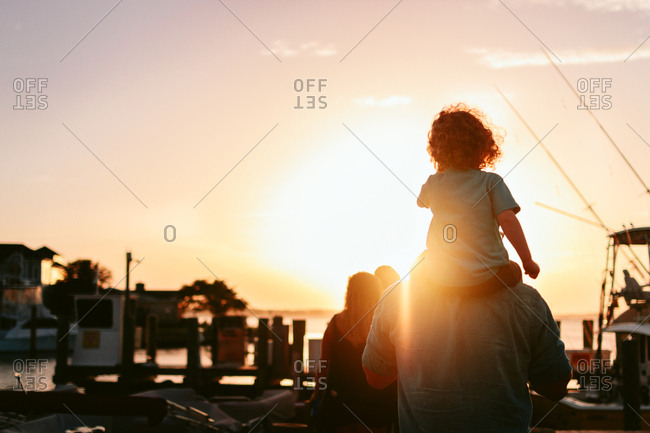 Boy on his father's shoulders at a marina at sunset