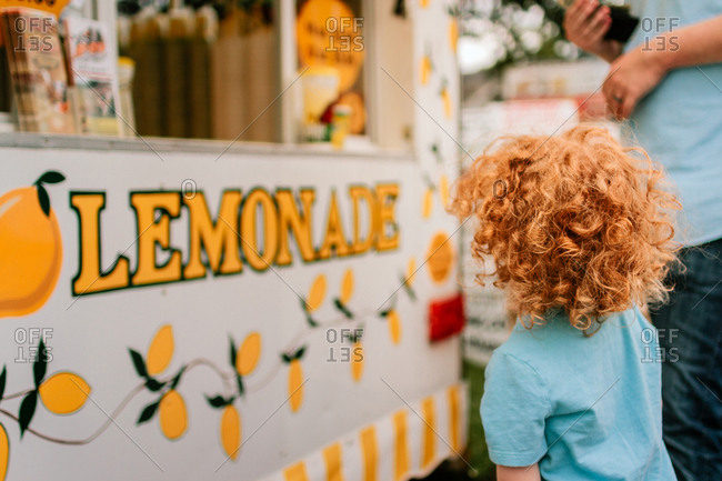 Father and son buying lemonade at a county fair