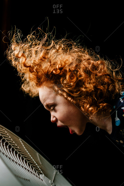 Boy with curly red hair yelling into an electric fan