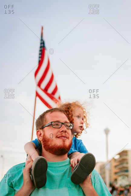 Child sitting on his father's shoulders with an American flag in the background