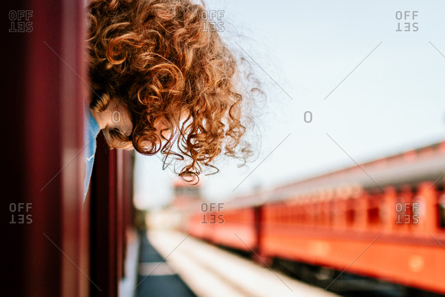 Boy hanging his head from the window of a train at a station