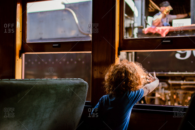 Boy waving to a train engineer from the window of another train