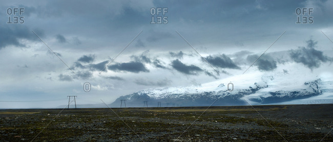 Power lines run across the vast open landscape of rural Iceland