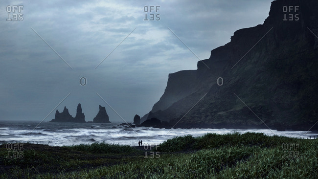 People silhouetted on beach at Reynisdragar, Iceland